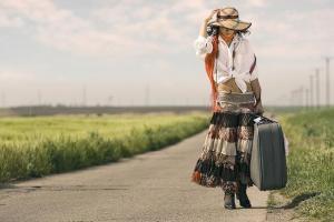 Mulher-andando-pela-estrada-com-mala-na-m%C3%A3o.1